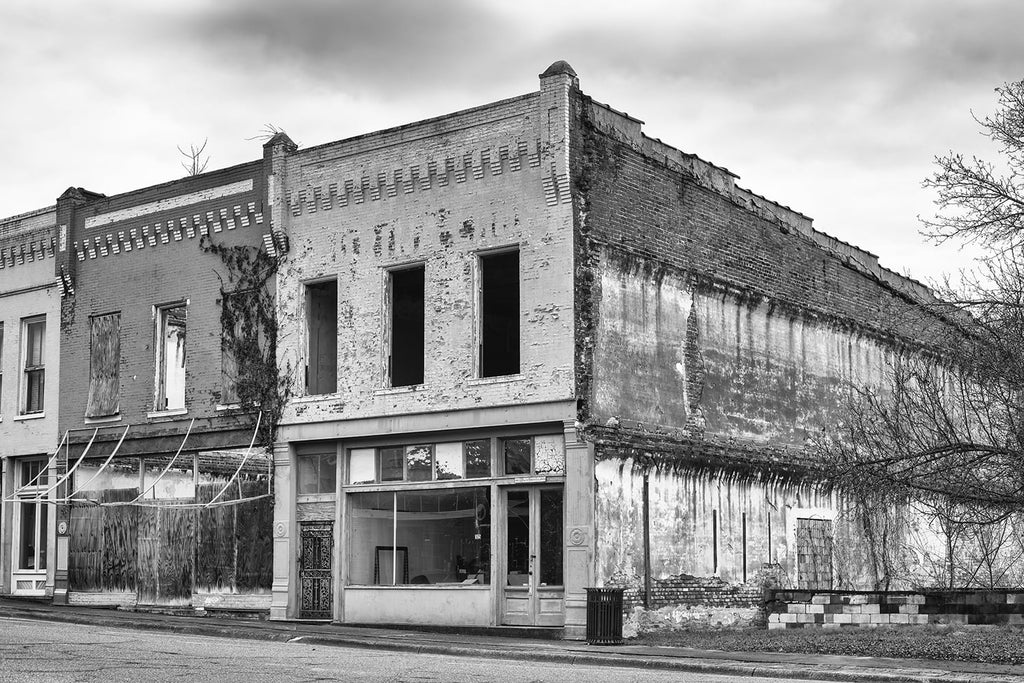 Black and white photograph of a block of historic but abandoned and derelict storefronts in a small town.