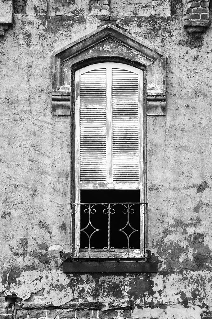 Black and white photograph of the second story window of an abandoned building with peeling paint, chipped bricks, and white shutters.