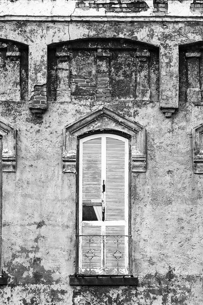 Black and white photograph of closed window shutters on an abandoned building with peeling paint and chipped bricks.