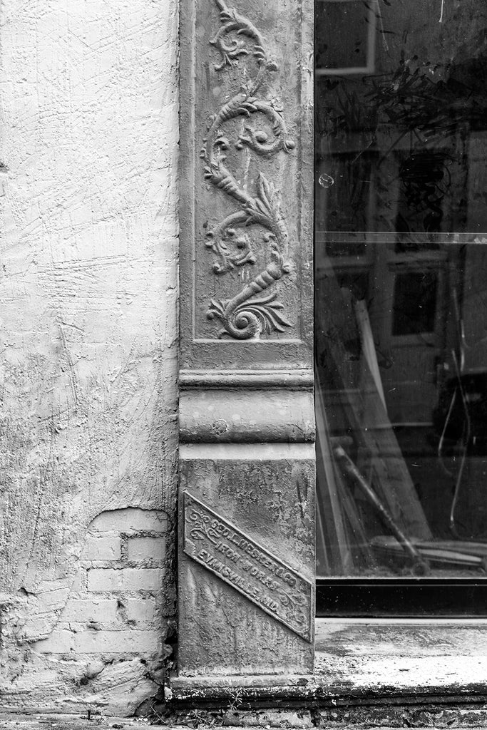 Black and white architectural detail photograph of an Mesker Iron Works metal column and nameplate on an abandoned building. Mesker Iron Works of Evansville, Indiana was one of the nation's leading sellers of iron work storefronts, tin ceilings, awnings, and other metal architecture elements. By 1915, they had sold storefronts into every state.