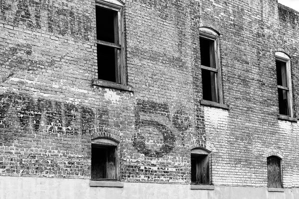 Black and white architectural detail photograph of the brick side of an abandoned building in a small town with a large fading wall ad advertising a price of 5 cents