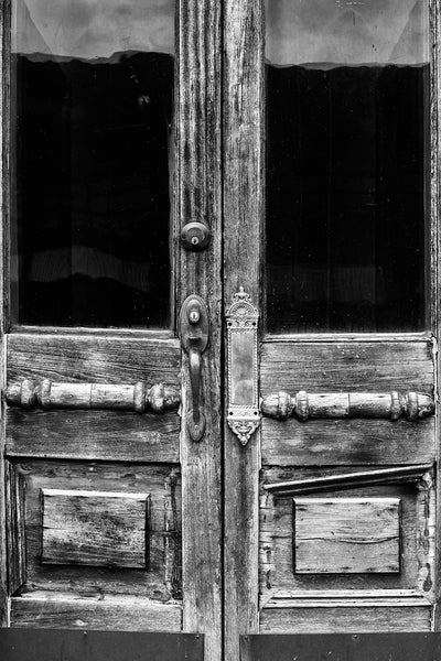 Black and white photograph of a two weathered and aged antique doors on a vacant storefront in a small town.