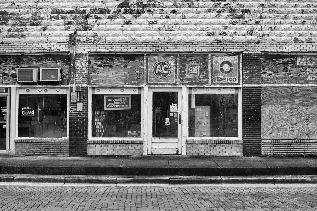Black and white architectural detail photograph of an apparently defunct auto parts storefront in a small town. Every quadrant of this photograph is rich with textures.