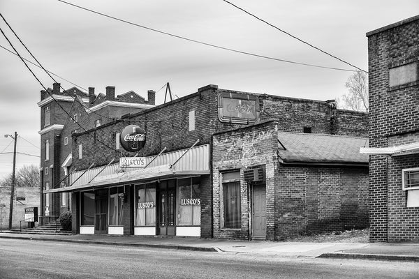 Black and white photograph of a block of historic brick buildings with several fading vintage signs in the Mississippi Delta at Greenwood.