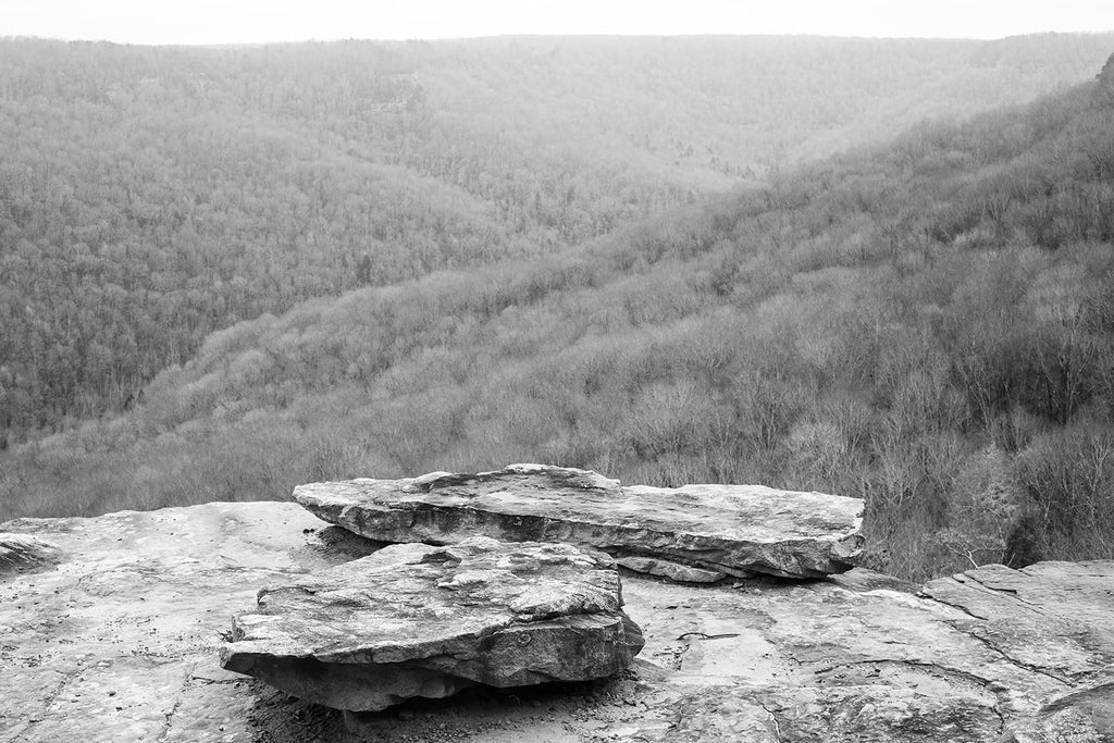 Black and white landscape photograph of a mountain vista seen from a rocky overlook.