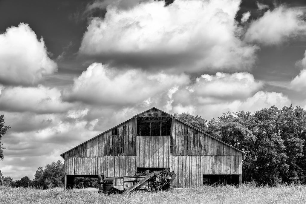 Black and white farm landscape photograph featuring a huge wooden barn built around 1900.