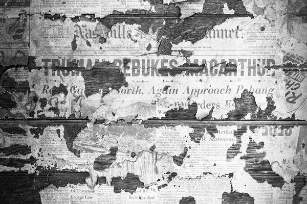 "Black and white photograph of a 1951 Nashville Banner newspaper pasted on the interior walls of an abandoned old farmhouse. The boldface headline says ""Truman Rebukes MacArthur."" The Nashville Banner was published from 1876 until 1998."