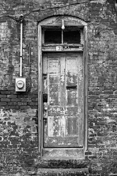 Black and white architectural detail photograph of a textured, old wooden door with chipped paint, found in an alley in a small town. Set into a brick wall with fading paint, this door has loads of detail and character.
