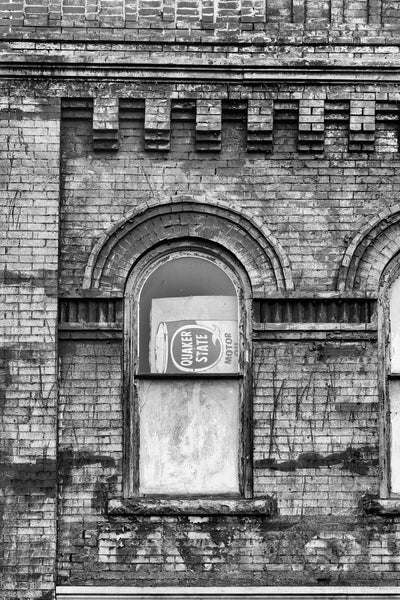 "Black and white photograph of an arched second floor storefront window with a sideways motor oil sign and faded paint that says ""Taylor"" on dark bricks."