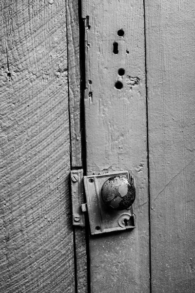 Black and white detail photograph of a rustic old wooden door with an antique door knob.