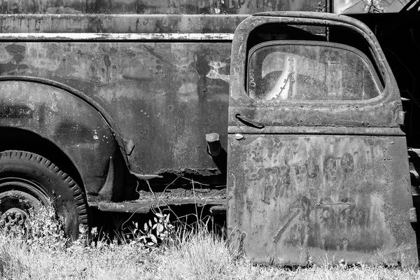 Black and white photograph of a beautifully rusting antique work truck abandoned in the grass
