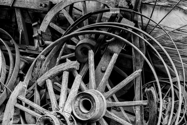 Black and white photograph of a jumble of old wooden wagon wheels with broken spokes and rims found on an old farm.