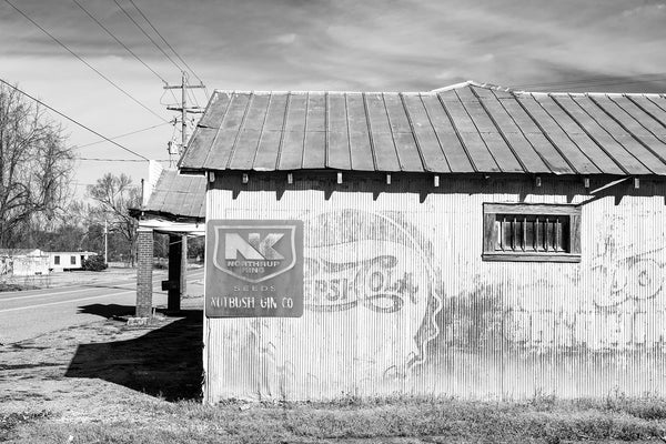 "Black and white photograph of an old cotton gin building located on Highway 19 in Nutbush, Tennessee, Tina Turner's birthplace. The side of the cotton gin features a vintage Pepsi-Cola sign dating between 1906 and 1940. This is probably the ""gin house"" mentioned in ""Nutbush City Limits."""