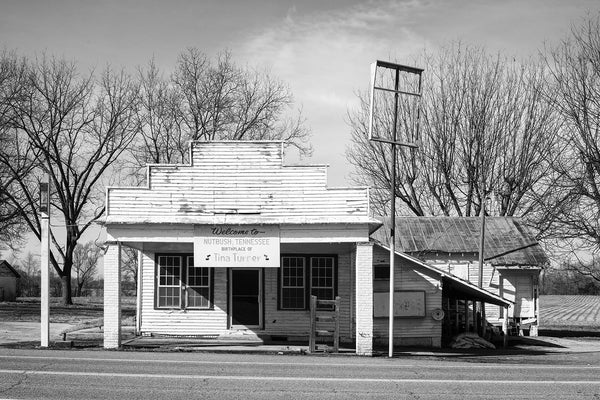 "Black and white architectural photograph of an abandoned old clapboard storefront on Highway 19 in Nutbush, Tennessee. An old sign on the building says, ""Welcome to Nutbush, Tennessee, Birthplace of Tina Turner."" Farm fields can be seen behind the building."
