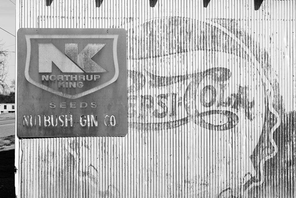 Black and white photograph of Vintage Ads on an Old Southern Cotton Gin Building
