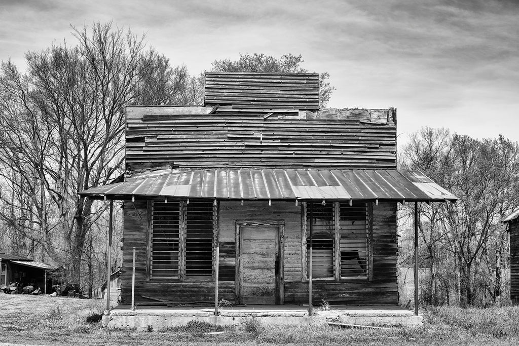 Black and white architectural photograph of an old, abandoned commercial building, most likely a storefront.