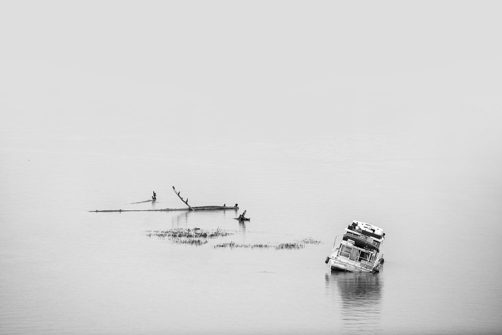 Black and white photograph of a boat sitting off-kilter after being run aground in the shallow part of a wide river.