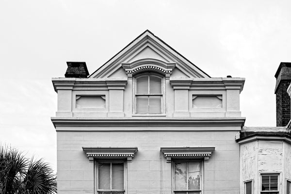 Black and white photograph of a historic house in Charleston with architectural details that are reminiscent of happy smiling eyes.