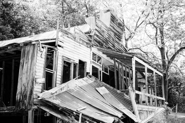 Black and white photograph of an abandoned and collapsing general store building in an old mining community ghost town now called Rush Historic District. This old general store was built between around 1900 to accommodate the miners and their families.