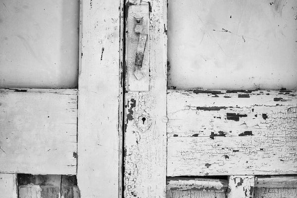 Black and white photograph of details in cracked paint and a bent ornate door handle on the doors of an abandoned building in a small town.