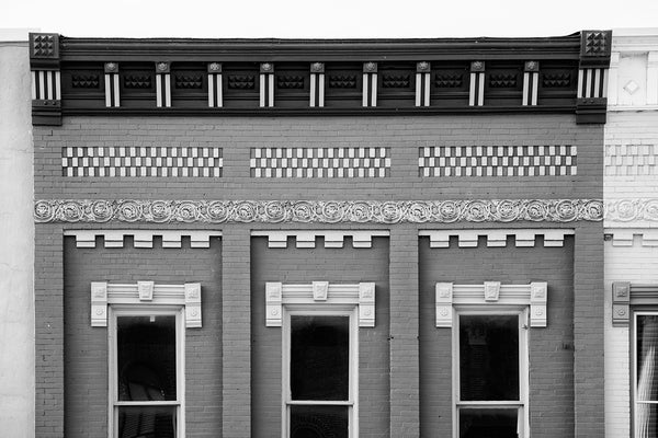Black and white architectural photograph of beautifully ornate details on the second story of a historic small town storefront.