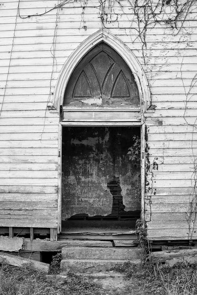 Black and white photograph of the open front entrance of an abandoned 1850s church in a Southern ghost town established along the Mississippi River in the 1820s.