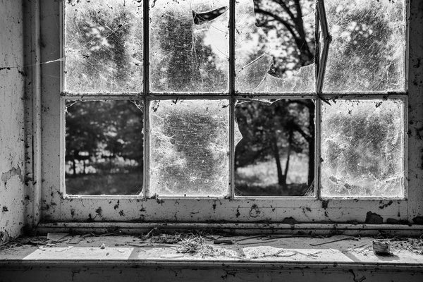 Black and white photograph of the view through the broken windows of an abandoned building in an 1800s-era southern ghost town.
