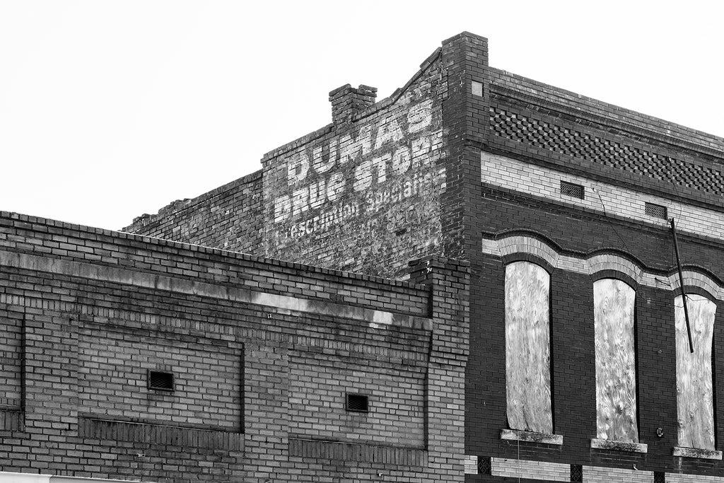 Black and white photograph of a fading old painted sign for Dumas Drug Store atop an abandoned building in downtown Natchez Mississippi