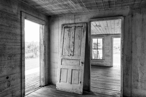 Black and white photograph of an old door leaning against the wall inside an abandoned farm house.