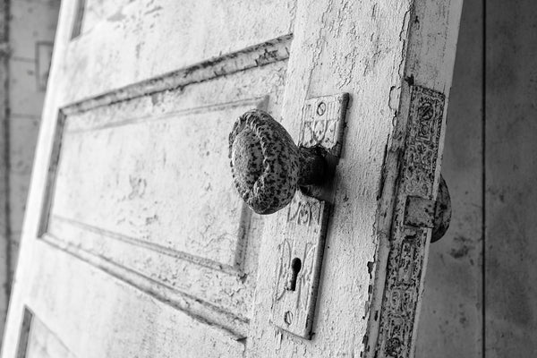 Black and white photograph of an ornate door knob on a detached door leaning against the wall inside an abandoned farm house.