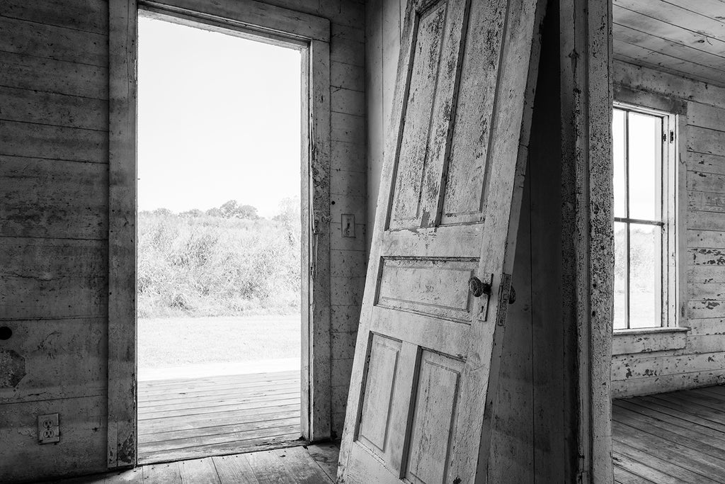 Black and white photograph of an old detached door leaning against the wall inside an abandoned farm house with fields visible outside.