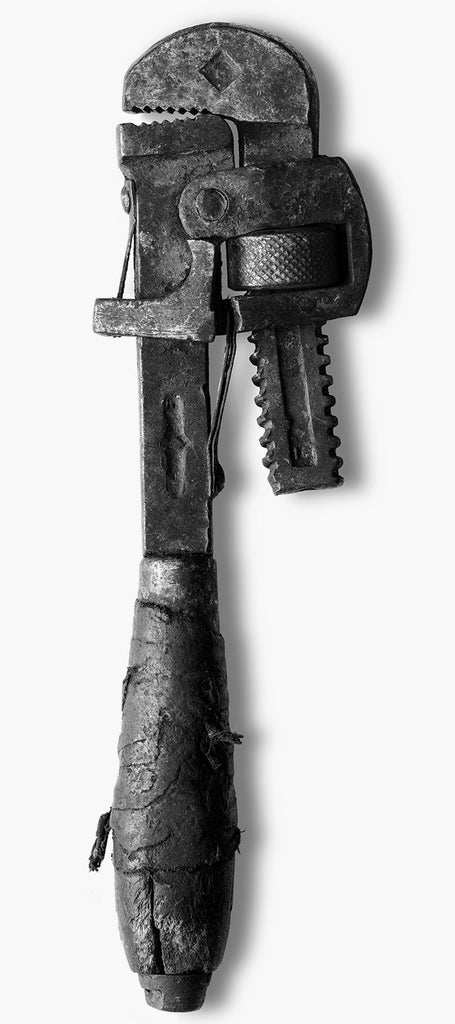 Large-format black and white photograph of an antique pipe wrench with a cracked handle that was repaired at some point with a fraying leather wrap.