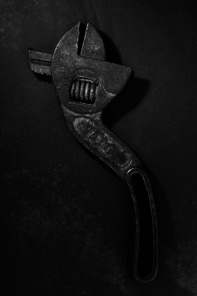 Dramatic black and white photograph of an antique S-shaped Westcott wrench in extremely low light.