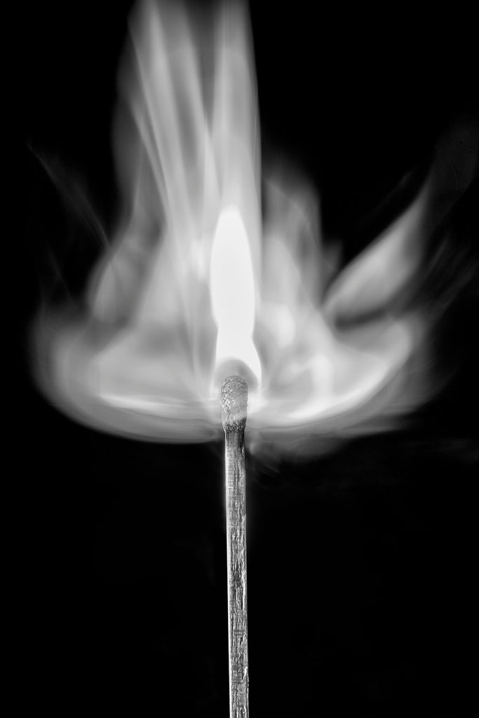 Minimalist black and white photograph of a wooden match at the exact instant of ignition.