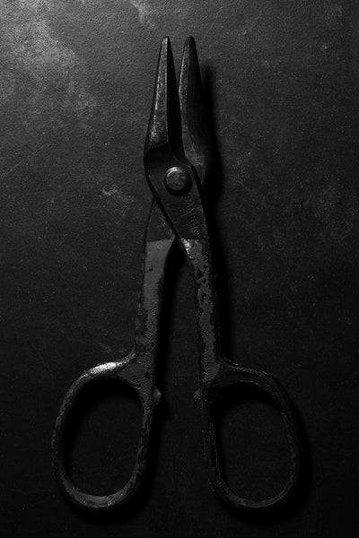 Dramatic black and white photograph of a pair of antique Samson 83 metal shears with red paint on the handles shot in low light