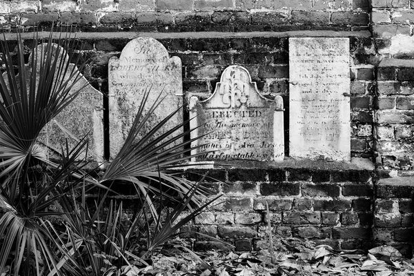 Black and white photograph of a row of headstones on a brick wall that borders Savannah's historic Colonial Cemetery. Established in 1750, the cemetery quickly expanded to six acres and was closed to interments in 1853. It now serves as a public park in Savannah's historic district.