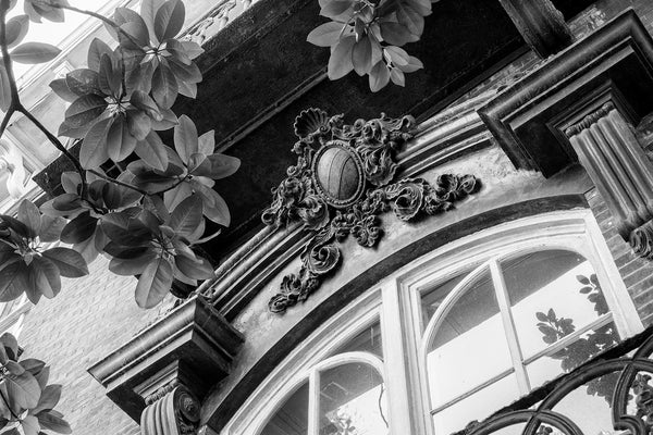 Black and white architectural detail photograph of an ornate decorative crest over the window of Savannah's historic and notorious Mercer-Williams House. Built in 1868, the house is famous as the location of the killing in Midnight in the Garden of Good and Evil.