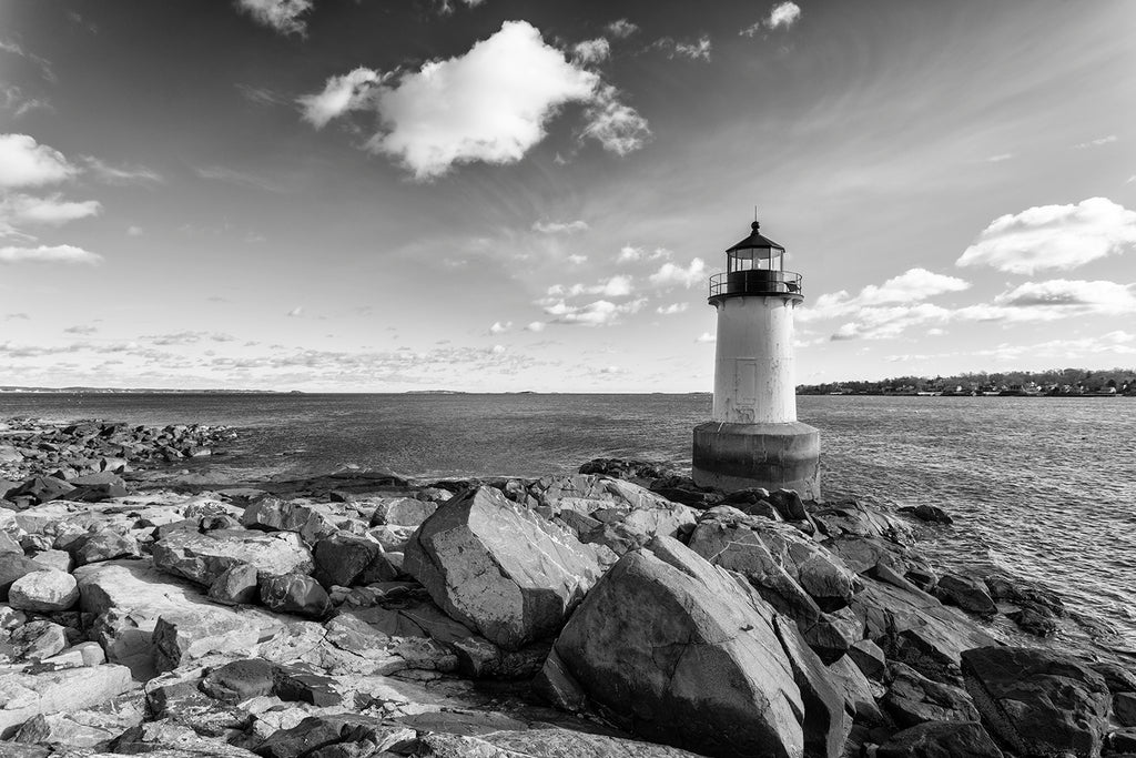 Black and white photograph of the rocky New England coast with ocean, clouds, and a small lighthouse.