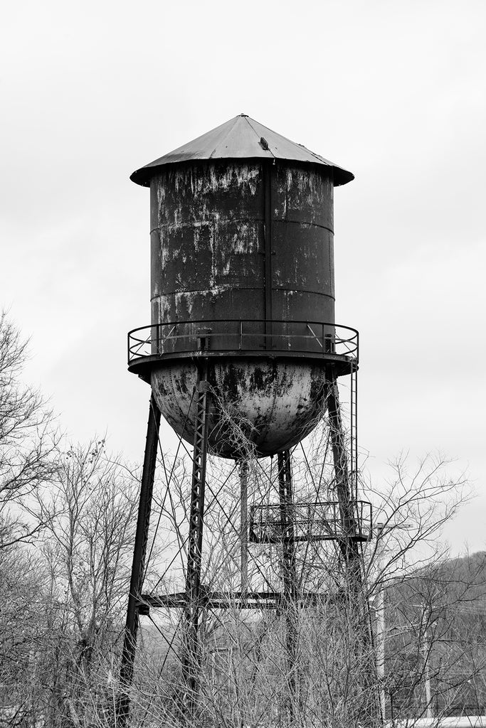 Black and white photograph of a rusty steel water tower among trees on the property of an old southern textile mill.