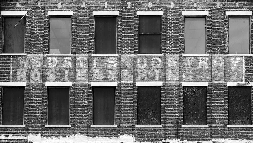Black and white photograph of a faded multiple-layer old sign on the brick wall of an old southern textile mill. The W.B. Davis Hosiery Mill operated from 1884-1974 in Ft. Payne, Alabama.