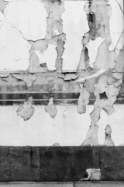 Black and white photograph of a downtown wall with paint and mural fragments peeling away in a beautifully random way.