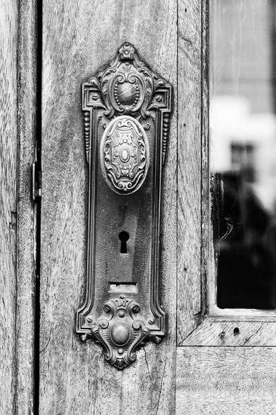 Black and white photograph of a beautifully decorative old door knob on an office building in a small city in the American South.