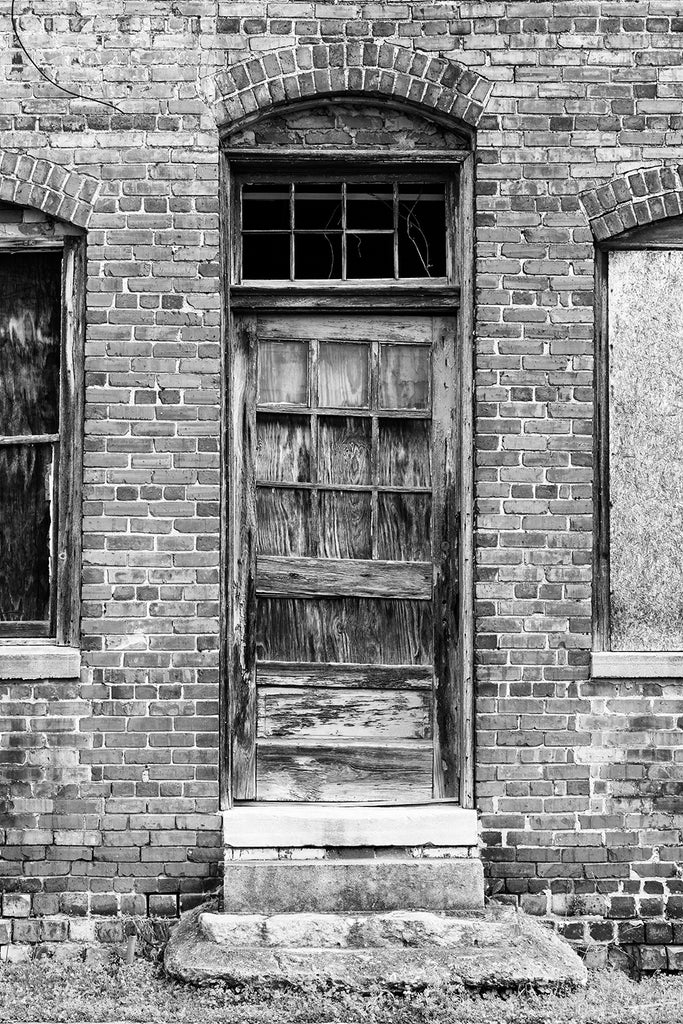 Black and white photograph of a weathered old wooden door on the exterior of an abandoned red brick mill building.