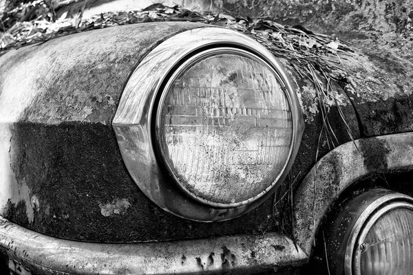 Black and white photograph of the headlight of a rusty antique automobile.