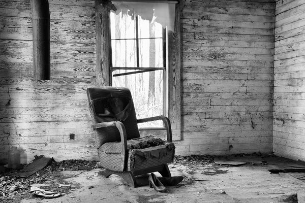 Black and white photograph of an old ruined chair and women's shoes inside an abandoned old house in the countryside.