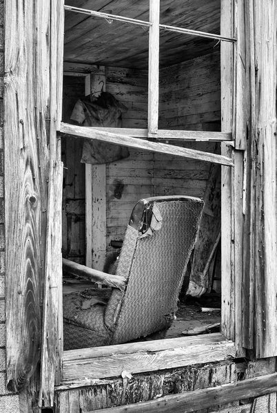 Black and white photograph looking into the window of an abandoned old house with a tattered chair and other left-behind items inside.