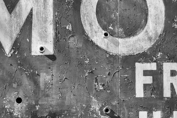 Black and white detail photograph of a textured old motel sign with peeling paint and ghost letters.