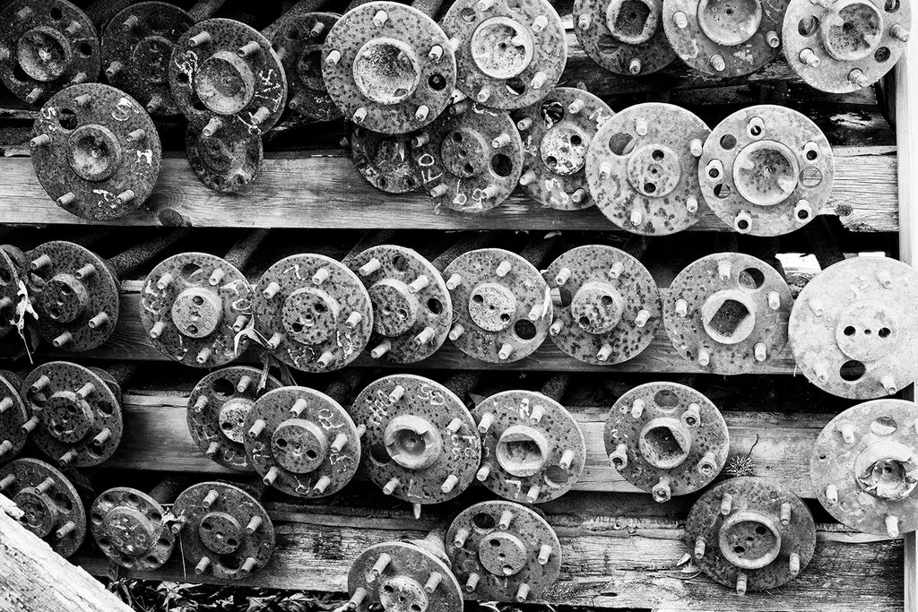 Black and White Photograph of 39 Rusty Antique Car Axles