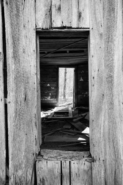 Black and white photograph looking into the open window of an old wooden farmhouse abandoned a long time ago in the woods.