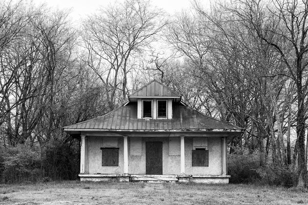 Black and white photograph of the front facade of an abandoned house with four posts on the front porch.